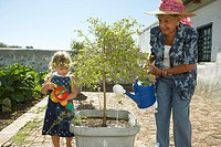 Girl Helping Her Grandmother Water Plants