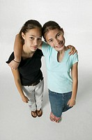 Two young female friends standing together, posing in studio, portrait, elevated view