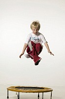 Boy (8-9), jumping with legs crossed on trampoline in studio, portrait