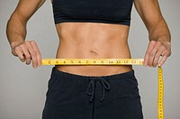 Woman holding tape-measure in front of abdomen, mid section