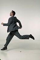 Businessman running in studio, portrait