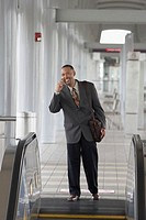 Mature man standing at the top of an escalator and talking on a mobile phone