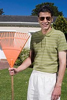 Suburban Man Holding Rake in Front of Home (thumbnail)