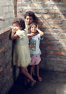 A trio of Nicaraguan children standing inside a brick structure as sunlight shines in from a window.