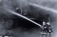 Two firefighters using hoses to fight a fire in an apartment building in Albuquerque, New Mexico.