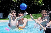 Several different aged children playing in an outdoor pool on a sunny day throwing a ball around.