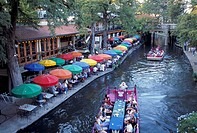 People eating, drinking and socializing under colorful umbrellas along the water and aboard barges in the water at Riverwalk in San Antonio, Texas