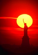 Silhouette of Statue of Liberty against sunset.
