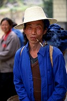 Man smoking pipe in rural market, portrait, wide-brim straw hat, small agrarian village near Wuxi, China, Asia, 042503