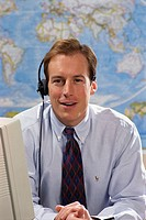 Businessman with headset in front of world map