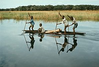 Four boys of the Libinza Tribe in canoe traveling to Mission Boarding School, Ngiri River area.