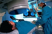 Patient lying on table and doctor using imaging machine with contrast to perform angioplasty and spiral CT scan.