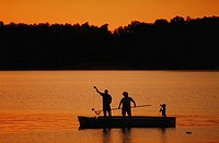 Silhouette of family fishing at sunset.
