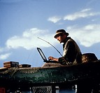 Fisherman in canoe working on laptop computer.
