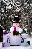 An inflatable snowman and snow kids outside a home during the winter Christmas season.