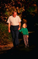 Grandfather walking outdoors with his grandson.