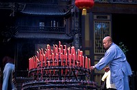 Side profile of a monk arranging candles, China