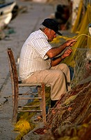 Side profile of a senior man mending a fishing net, Crete, Greece