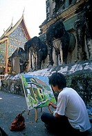 Side profile of a young man painting on an easel in front of a temple, Thailand