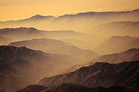Nepal, Kathmandu Valley, overhead view of hill tops silhouetted among yellow haze and sky.