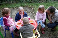 Group of young children having a picnic in the garden