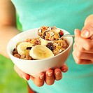 Woman eating muesli with banana