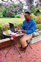 Man Sitting in Back Yard with Laptop