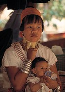 Kayan woman (´giraffe woman´) with brass rings around her neck, bottle-feeding baby