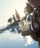 Man holding cocktail glass and looking at empty pool, sunset