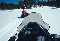 Driver's point-of-view as he follows another snowmobile towards the woods near Mammoth Lakes, CA.