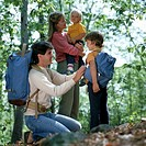 Father adjusting son's backpack and mother holding younger child as they prepare to go hiking in the woods.