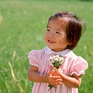 A smiling young Asian girl wearing a dress with pink stripes holding a handful of wildflowers.