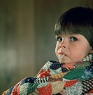 Young boy sits wrapped in a colorful blanket while having his temperature taken with an oral mercury thermometer.