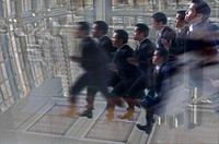 Blurred view of several Asian businessmen wearing suits running.