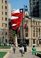 As Chile´s flag flies over head, pedestrians stroll through Constitution Plaza, near ´La Moneda´ (Presidential Palace) in downtown Santiago, Chile.
