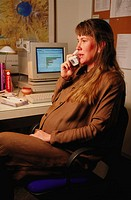 Pregnant woman talking on phone in home office