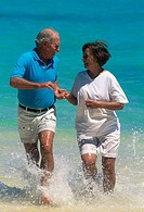 Senior couple at the beach, jogging through shallow water
