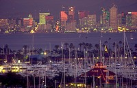 San Diego skyine at dusk with sailboats and marina in the foreground.