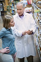 Health Food Store Pharmacist Assisting Woman
