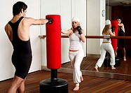 Young man and woman hitting the punching bag