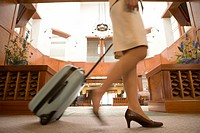 Woman pulling wheeled suitcase, low angle view, blurred Image