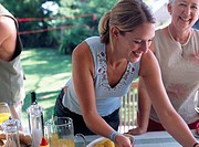 Smiling Woman Leaning Over Table at Barbecue