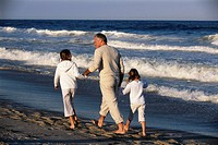Father Walking on Beach with Daughters