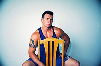 Young Caucasian muscle man with tattoos sitting on chair