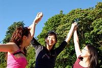 3 asian girls raising hands together