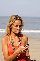 Beautiful blonde woman looking upset at a phone on an beach in India