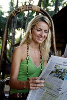 Beautiful blonde woman sat outside reading the paper, shot in the morning in India