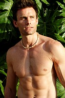 Vertical shot of good looking caucasian man with toned torso standing in front of tropical green leaves in India