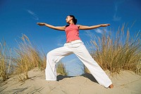 Young woman exercising on sand dune (thumbnail)