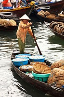 A woman rowing boat full of fish for sale at fishmarket, Hoi An, Vietnam, South East Asia.